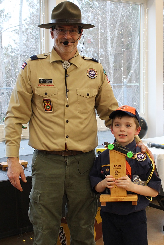 Mason Hilton won the Second Place trophy for his tanker derby car with a camouflage paint job and green wheels. Mason Hilton is pictured (at right) with Cubmaster Chris Gates (at left). (Rachel Hunter photo)