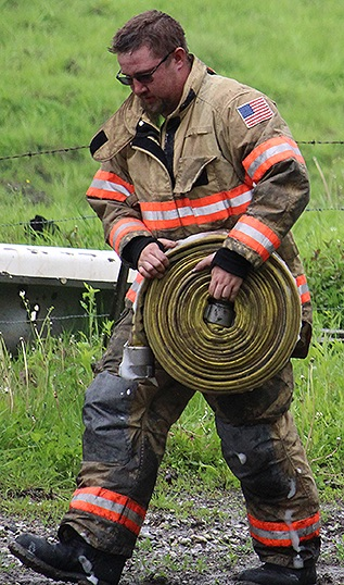 Local fireman carrying hose on the fire scene.