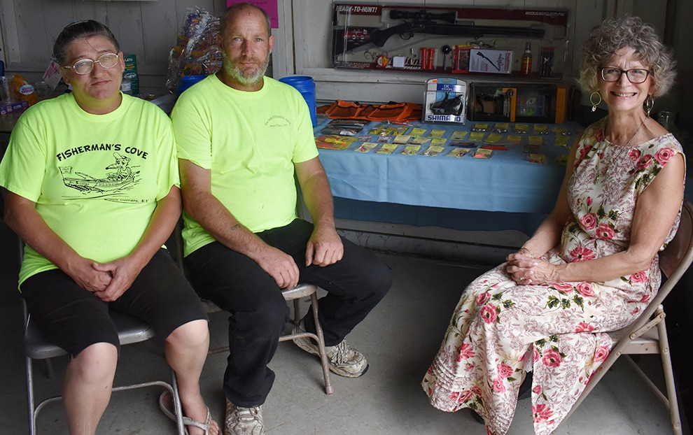 Joanna Nosworthy, Bill Law, Fisherman's Cove owners, and Rebecca Reynolds, President of the Macomb Historical Association, seated in front of all the wonderfully donated items from Fishman's Cove. (photo by Jessyca Cardinell)