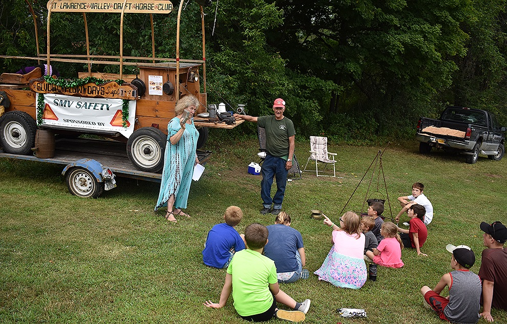 Richard Clement of Fowler with his wagon filled with various antique items, along with Debbie Tulley, Macomb Historical Association member, test the youngsters memory as they list of all the items found. Once finished the kids were asked to fill out a paper with as many as they could remember, the one who knew the most won. (photo by Jessyca Cardinell)