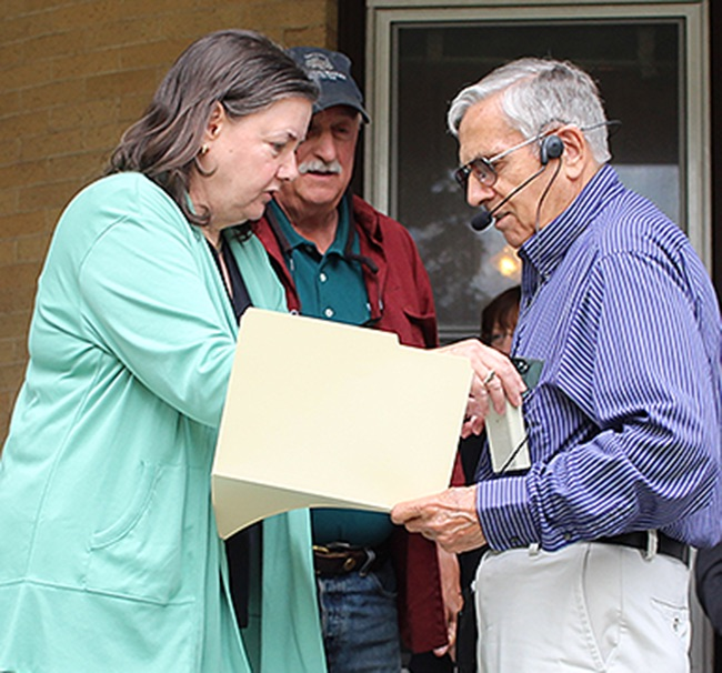 Shari Barnhart of Rainbow Tech Designs (Gouverneur Museum webmaster) fits Gouverneur Historian Joe Laurenza with a microphone so that all could clearly hear the information presented during the historic walking tour on Saturday, August 24. The picture was taken before the walk commenced from the Gouverneur Museum. Looking on from behind is St. Lawrence County Historical Association President Lance Rudiger. (Rachel Hunter photo)
