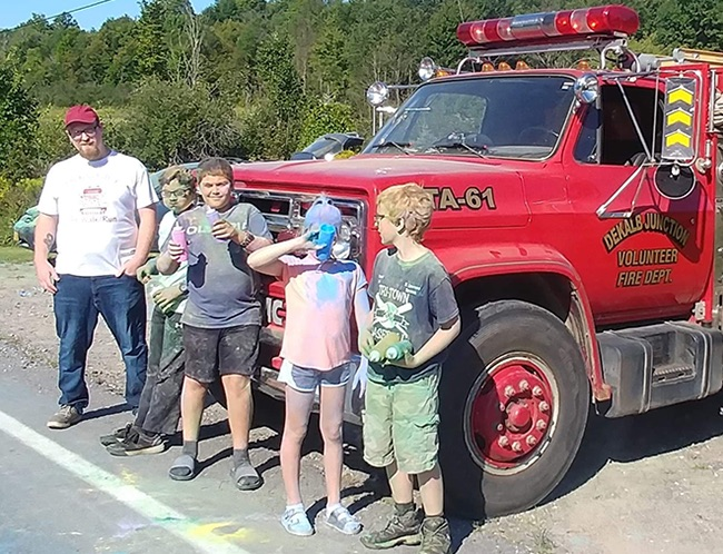 Local boy scouts and Youth Advocate Program members stand in front of a DeKalb Junction Volunteer Fire Department water tanker readying to spray color at the participants in the 5K Color Run/Walk on Sunday, August 25. (Photo provided)