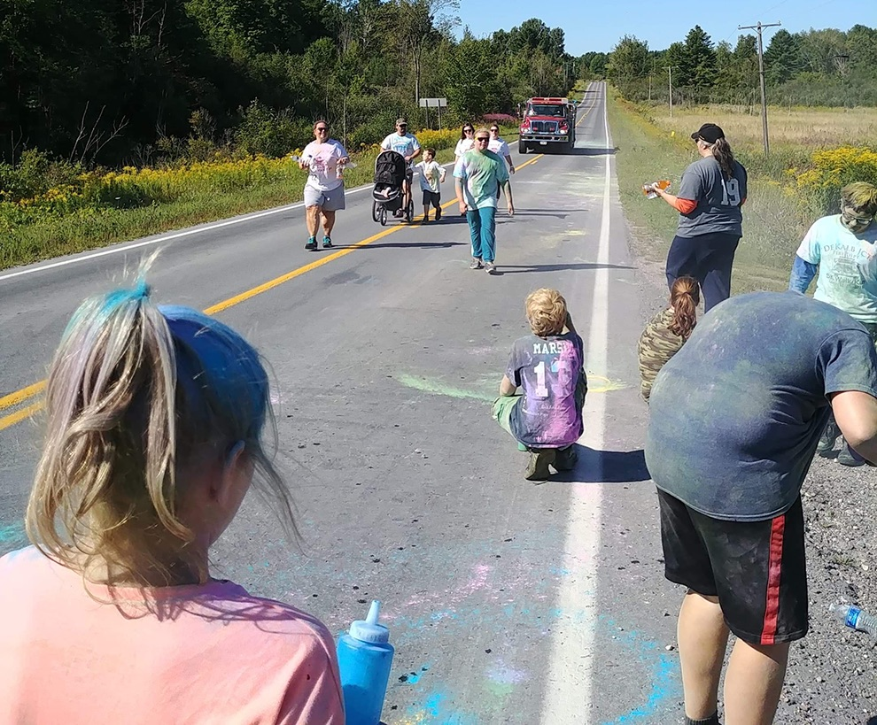Color sprayers await as participants in the Color Run/Walk approach, followed by a DeKalb Junction Volunteer Fire Department truck. (photo provided)
