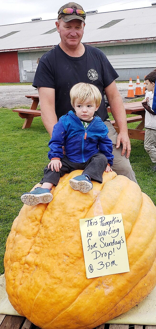DeKalb Junction Fire Chief Bob Drake enjoying the 2019 Gouverneur Pumpkin Festival on Saturday, September 28 with his grandson, Robert, at the Gouverneur Fairgrounds. Robert is pictured sitting on the giant pumpkin that was dropped on Sunday, September 29. (photo provided)