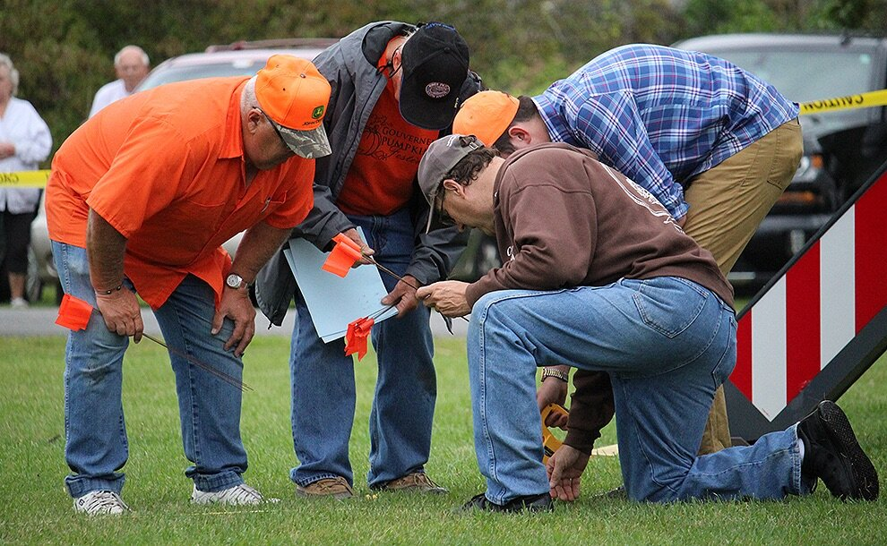 Past Fair President Lyle Hotis writes down the distance and number of a golf ball that was one of the furthest traveled after the first 2019 Gouverneur Pumpkin Festival Giant Pumpkin Drop. Also pictured, Fair Director Dave Bishop of DeKalb, Fair Associate Director Nicholas Whitney of Canton, and Fair Manager Don Peck of Gouverneur. (Rachel Hunter photo)