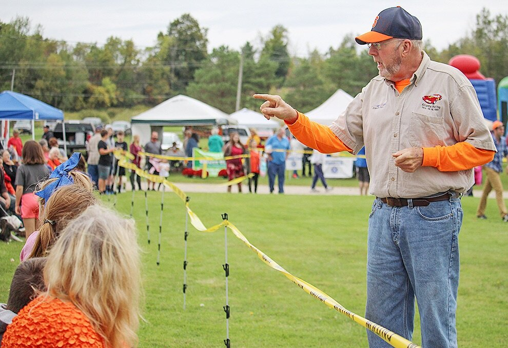Gouverneur Chamber Director Gale Ferguson encouraging festival-goers to be prepared to duck in case of flying pumpkin meat just before the first 2019 Gouverneur Pumpkin Festival Giant Pumpkin Drop. (Rachel Hunter photo)