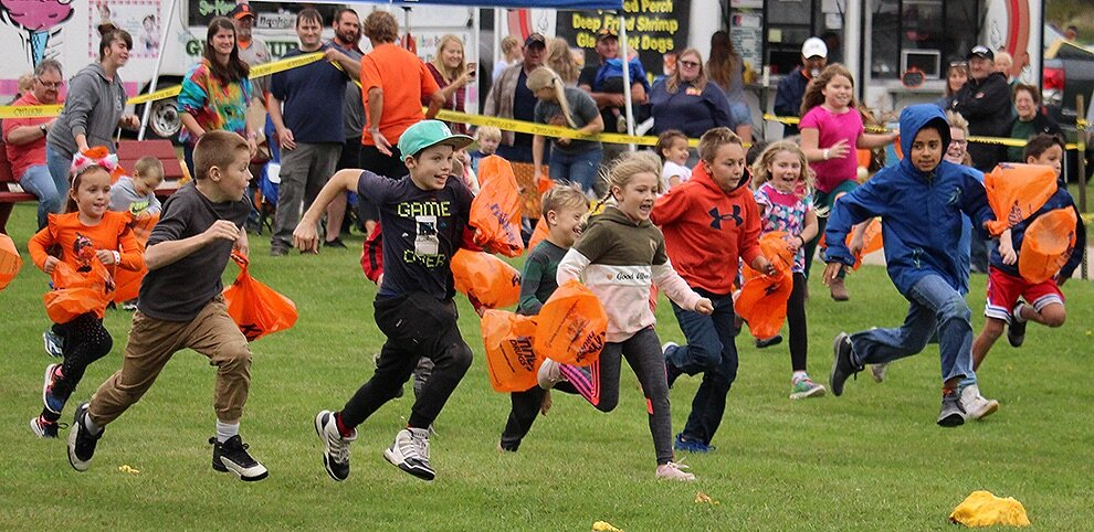 Youngsters run to collect the golf balls after the first 2019 Gouverneur Pumpkin Festival Giant Pumpkin Drop on Saturday, September 28 at the Gouverneur Fairgrounds. (Rachel Hunter photo)