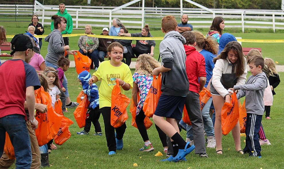 Local children collecting golf balls by the giant pumpkin drop zone. (Rachel Hunter photo)