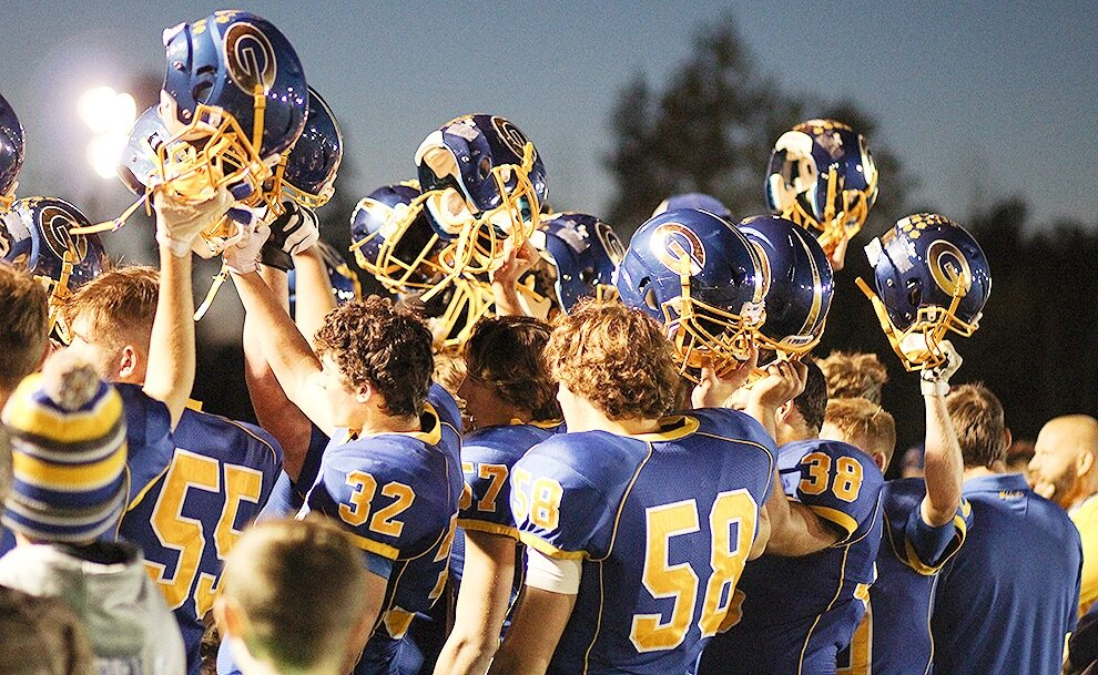 Gouverneur Wildcats lift their helmets in unison as they sing the GHS Alma Mater Song under the lights on the Frank LaFalce Field. (Rachel Hunter photo)