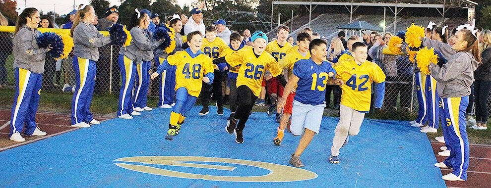 Gouverneur Pee Wee Football players were invited to lead the Gouverneur Wildcat Varsity Football Team onto the Frank LaFalce Field on Friday, October 11. The youth were inspired to develop their athletic skills during their talks with the varsity football players and GHS coaching staff before the game. Pictured: Youth football players run through the open gate – cheered on by varsity cheerleaders – as they ran onto the Frank LaFalce Field. The youth then joined the rest of the Gouverneur community in cheering on the varsity football players to a shutout win over the Massena Red Raiders. The local youngsters will undoubtedly remember this special opportunity for years to come, especially since it was the first time Gouverneur witnessed a game under the lights on Frank LaFalce Field. (Rachel Hunter photo)