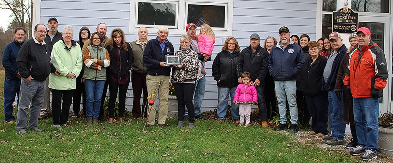 The dedication of a Jane Magnolia Tree in memory of longtime youth advocate, Laurie Allen, drew many local residents to the Gouverneur Community Center to remember Allen's life and legacy. Pictured: Gouverneur Mayor Ronald McDougall and Donna Sawyer, Laurie Allen's best friend, hold the dedication plaque behind the magnolia tree. They are surrounded by other community members, family members, friends, and local dignitaries (including Town of Gouverneur Supervisor Dave Spilman, Jr., Town of Gouverneur Deputy Supervisor Eldon Conklin, Village of Gouverneur Clerk/Treasurer Barbara Finnie, Village of Gouverneur Chief of Police Laurina Greenhill). (Rachel Hunter photo)