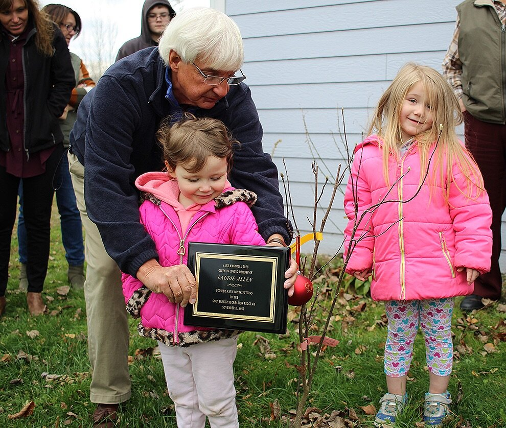 Looking to the future, Gouverneur Mayor Ron McDougall encourages Laurie Allen's grandchildren – Laurie Ruth Allen and Harley Quinn Allen – to stand by the Jane Magnolia tree that was dedicated last Saturday, November 2 in front of the Gouverneur Community Center. (Rachel Hunter photo)