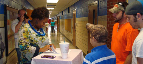 Tara King, principal of West Hartsville Elementary School, greets a family at the Back to School Bash, August 2013