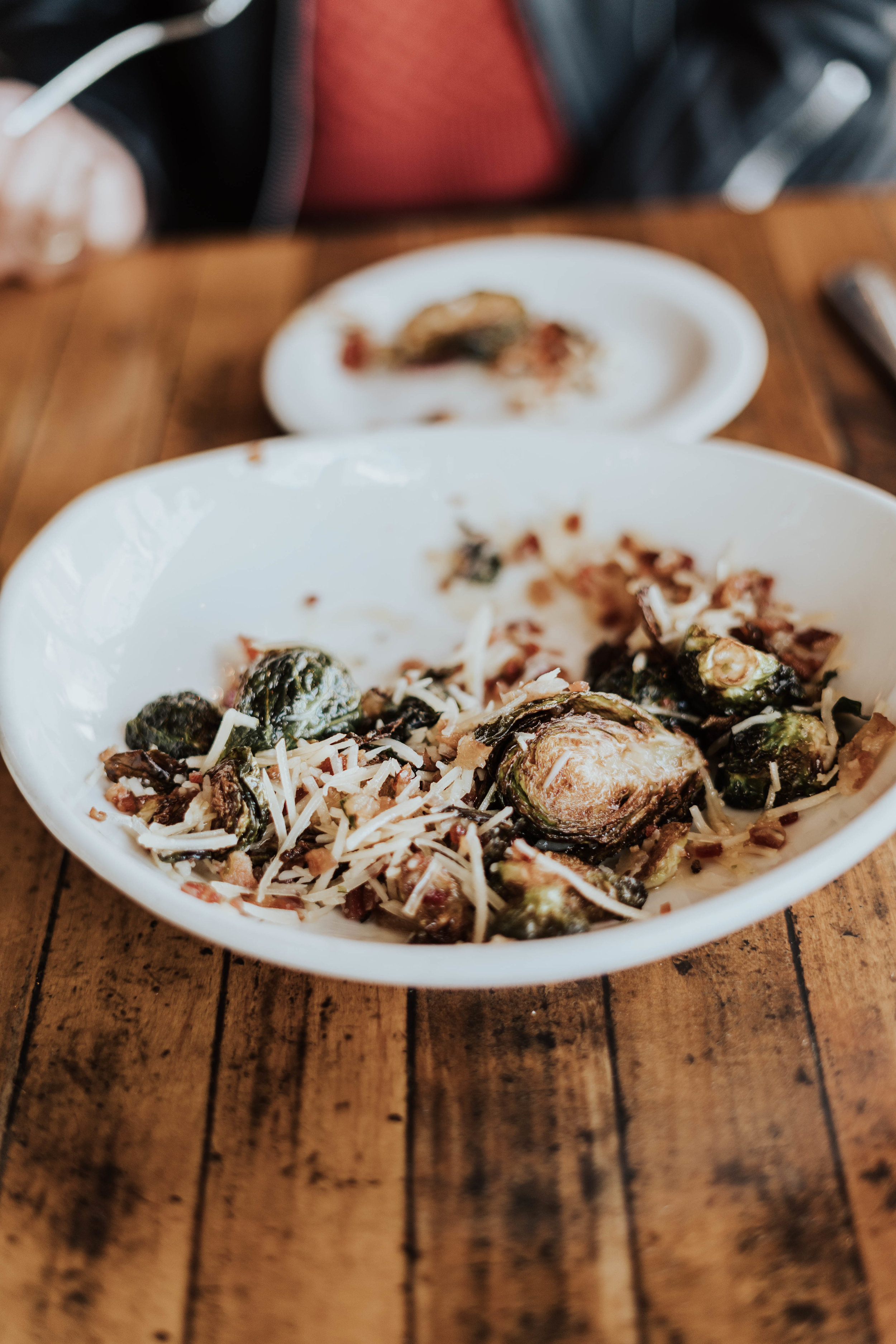 Delicious fried brussels sprouts with bacon, parmesan, and honey drizzle at Benchmark Eatery, Santa Barbara