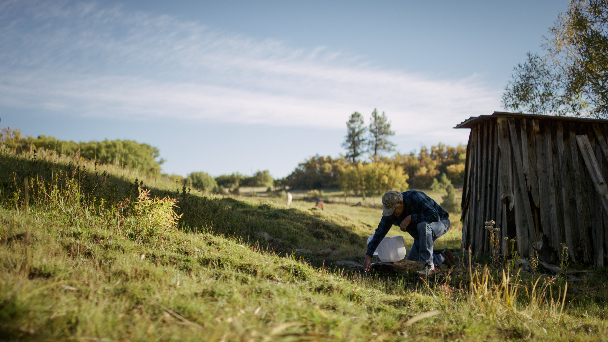 Tito Naranjo collects water from a spring on his property in Mora, NM.
