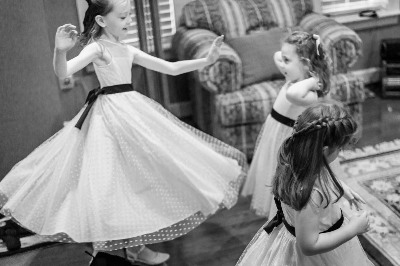 Flower girls twirl in their dresses before the ceremony at home in fairfax, virginia