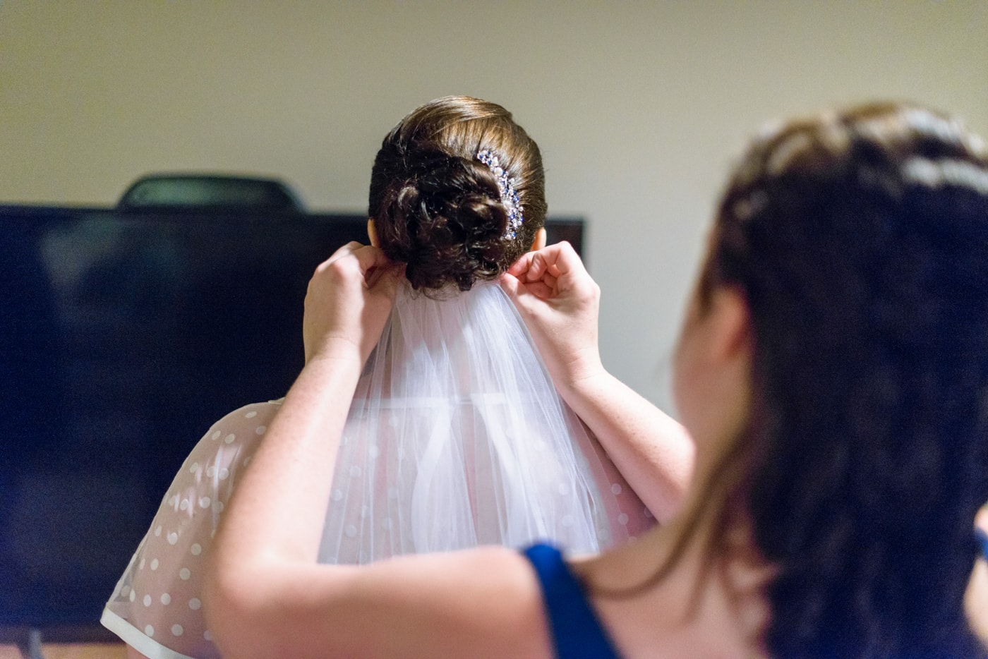 A bridesmaid puts on the bride's veil as they get ready in fairfax, virginia