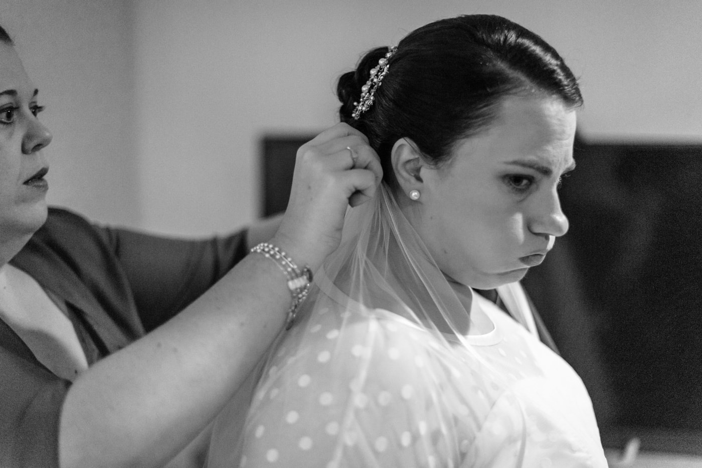 A bridesmaid pins the veil on to the bride as they get ready in fairfax, virginia