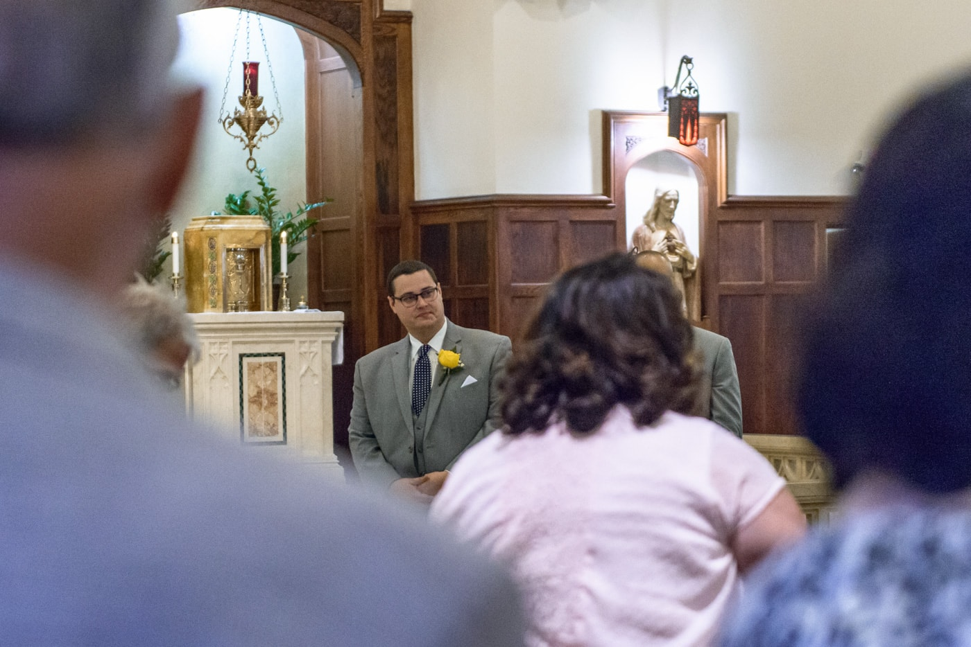 The groom gets emotional as he watches his bride walk down the aisle at St James Catholic Church in Falls Church, Virginia