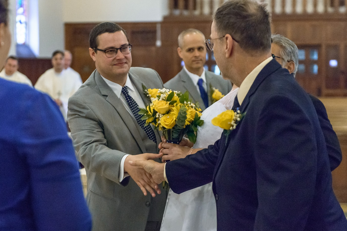 The groom shakes hands with the bride's father during wedding ceremony at St James Catholic Church in Falls Church, Virginia