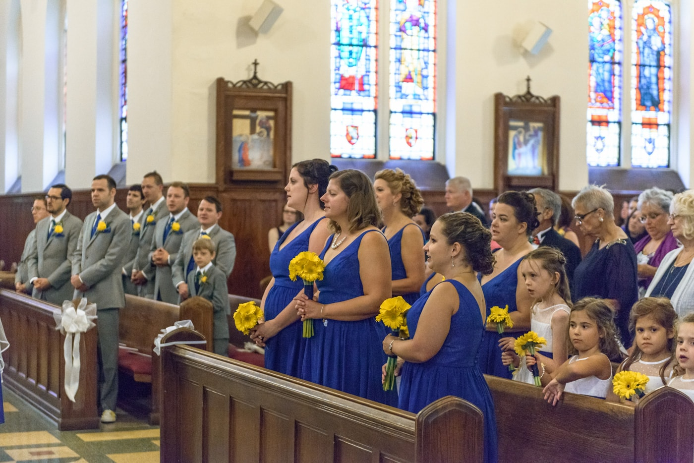 The wedding party standing in the pews during a wedding ceremony at St James Catholic Church in Falls Church, Virginia