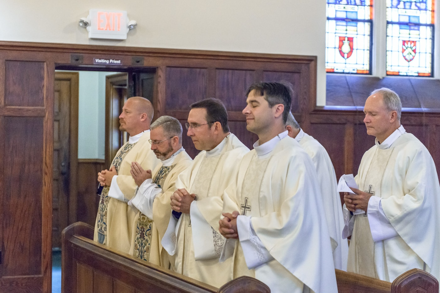 Six priests in the pews during a wedding ceremony at St James Catholic Church in Falls Church, Virginia
