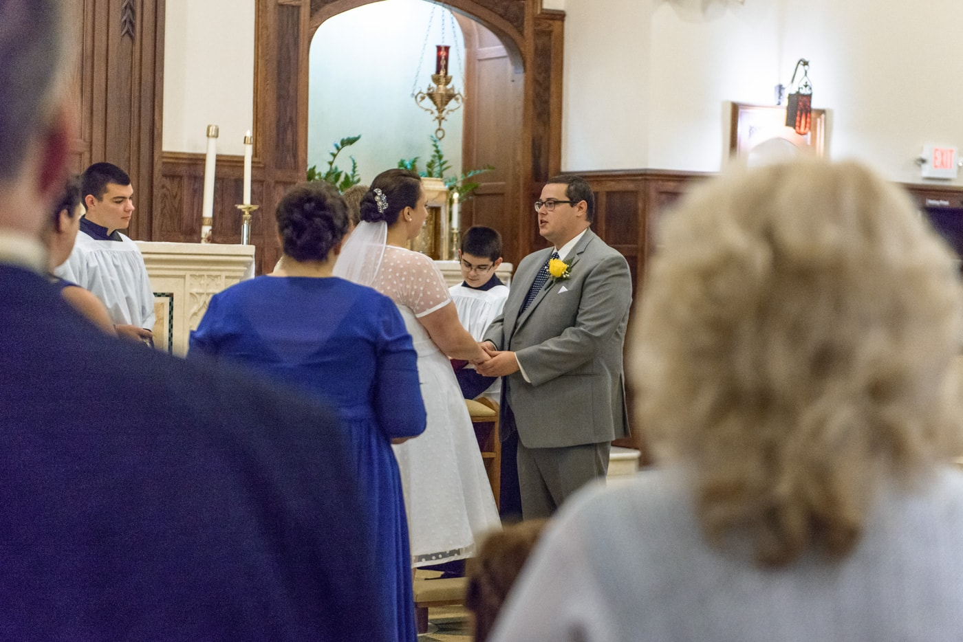 The bride and groom hold hands in front of the altar during their wedding ceremony at St James Catholic Church in Falls Church, Virginia