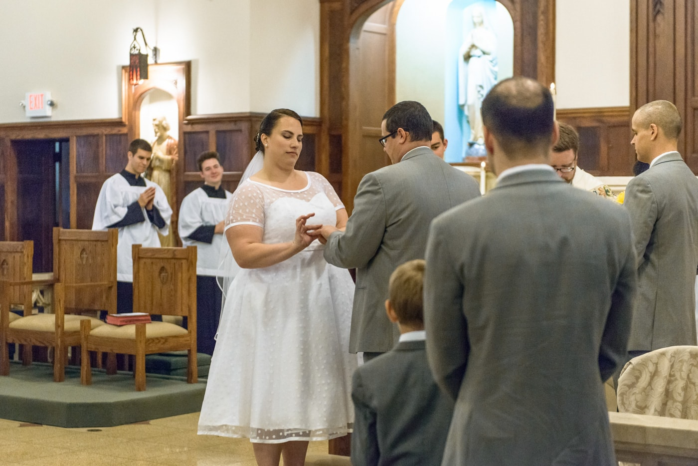 The bride puts the ring on the groom's finger during exchanging of rings at wedding at St James Catholic Church in Fairfax, Virginia