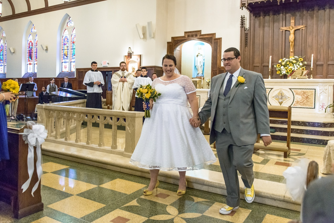 The bride and groom face their guests at the end of their wedding ceremony at St James Catholic Church in Falls Church, Virginia