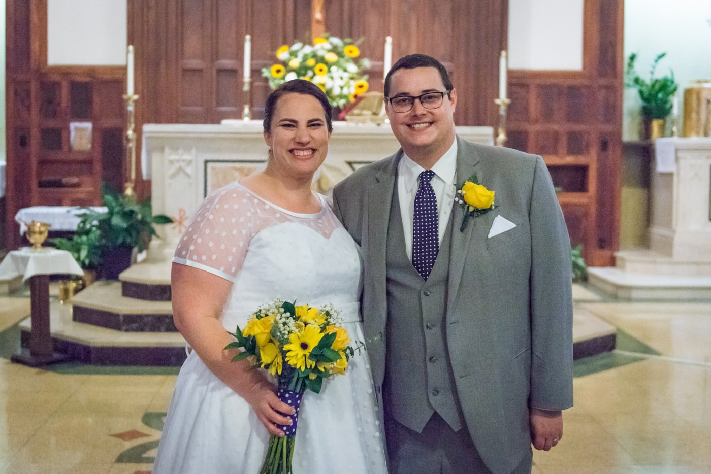 The bride and groom post for a traditional portrait at St James Catholic Church in Falls Church, Virginia