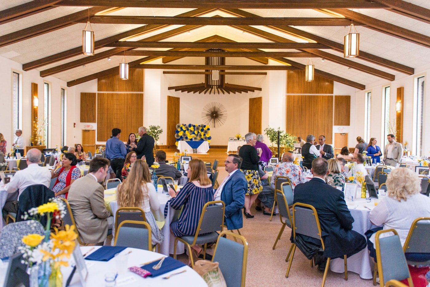 Wide shot of a yellow and blue brunch wedding reception at St Mark Catholic Church in Vienna, Virginia