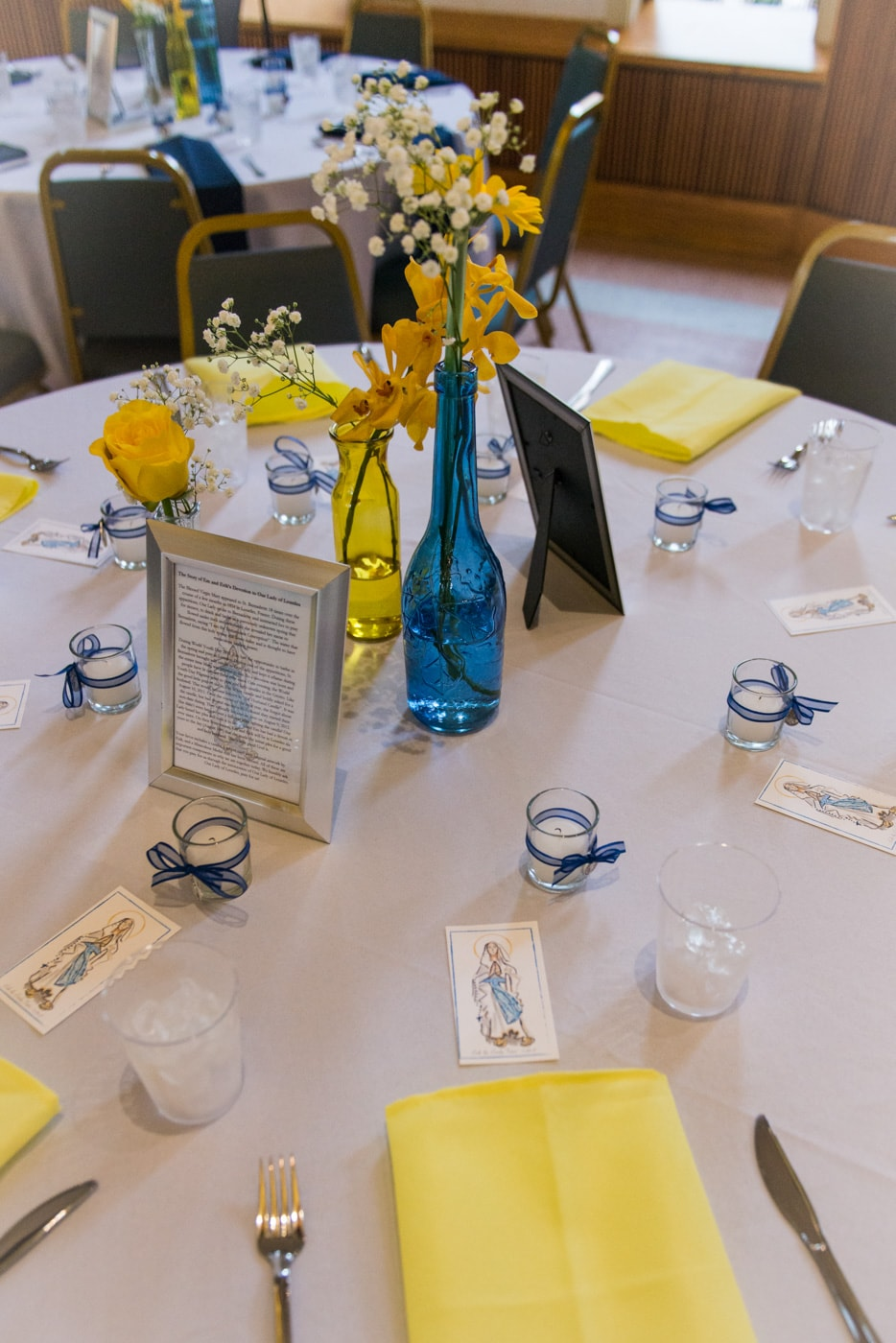 Detail of table settings with blue and yellow vases and candles at a brunch wedding reception at St Mark Catholic Church in Vienna, Virginia