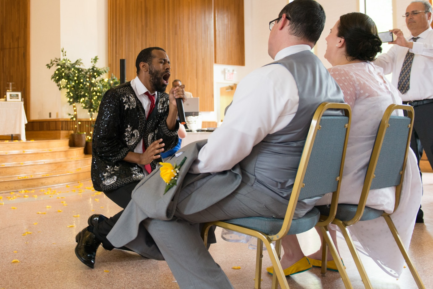 A wedding guest performs a lip sync for the seated bride and groom at St Mark Catholic Church in Vienna, Virginia
