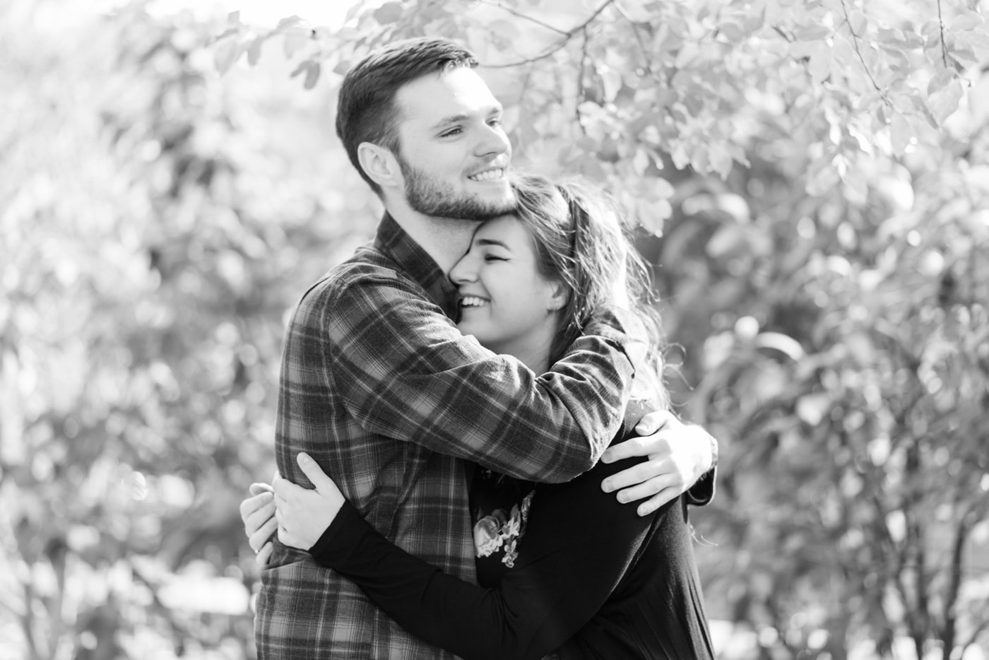 Black and white of a young couple embracing and laughing in Old Town Alexandria