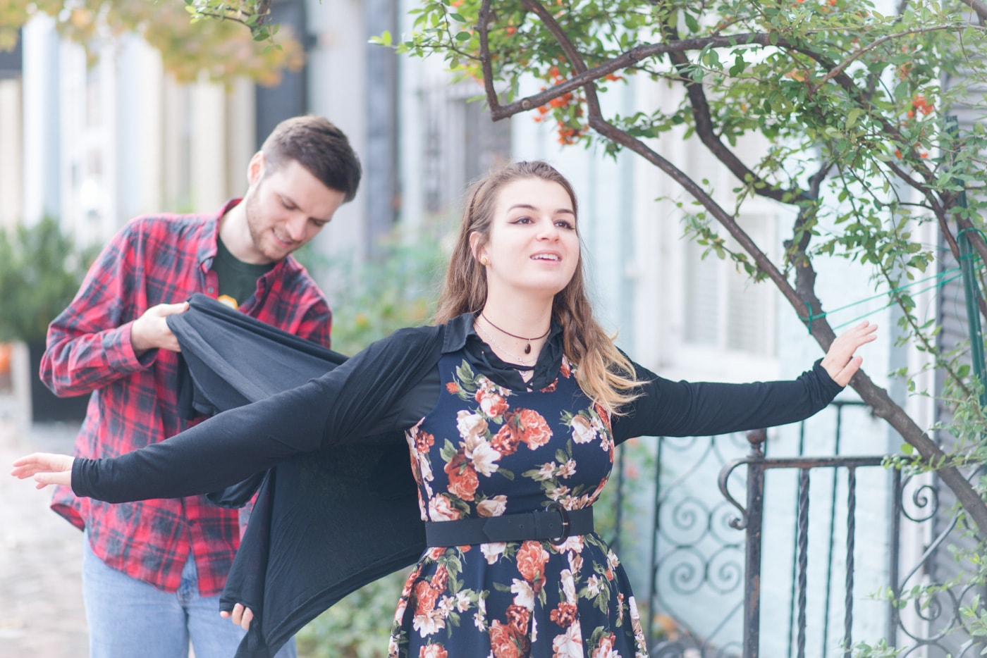 A young woman holds her arms out and looks up like she's flying as her boyfriend tries to hold her sweater out like it's flying in the wind in old town alexandria