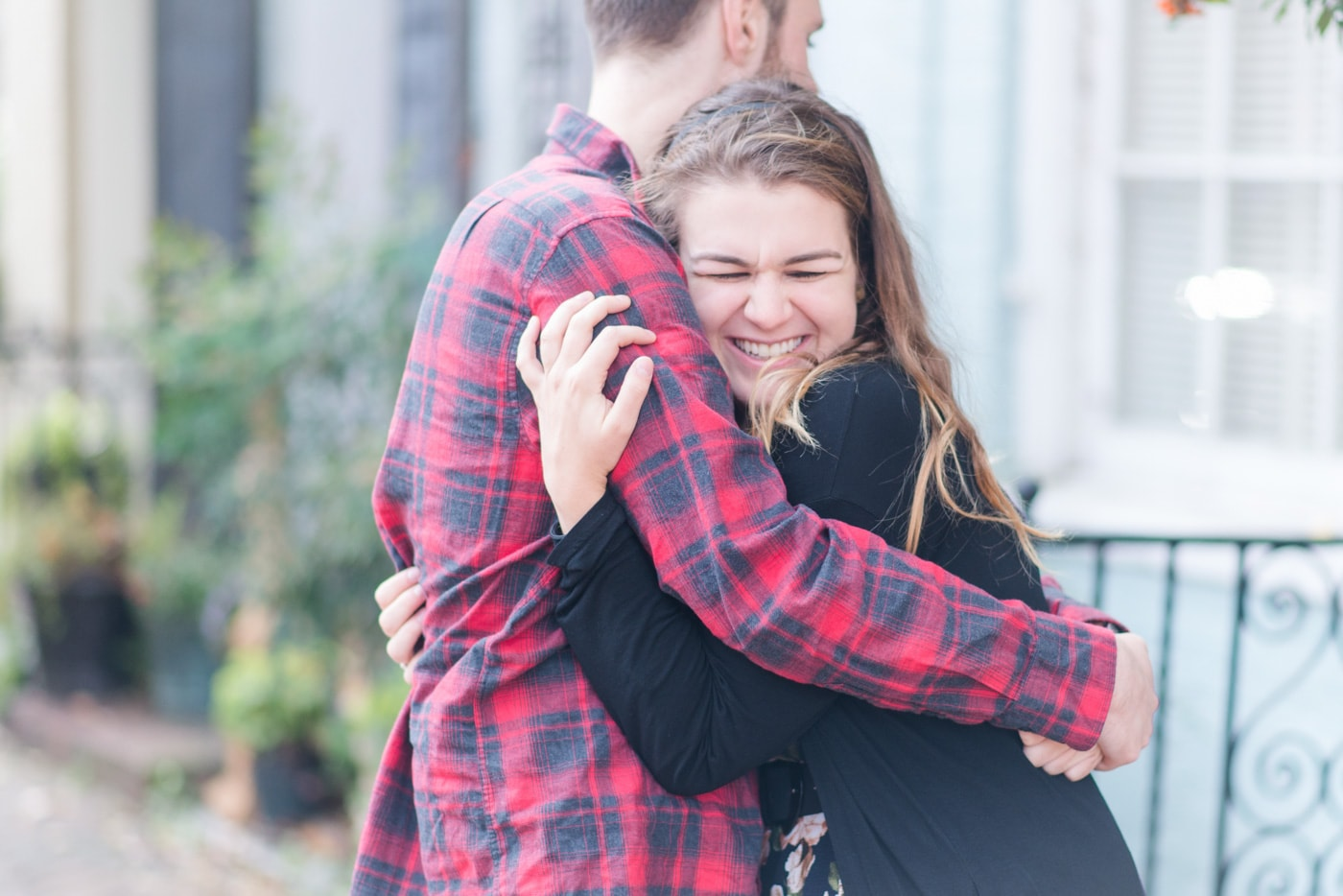 A young woman squeezes her boyfriend in a tight hug on the streets of Old Town Alexandria