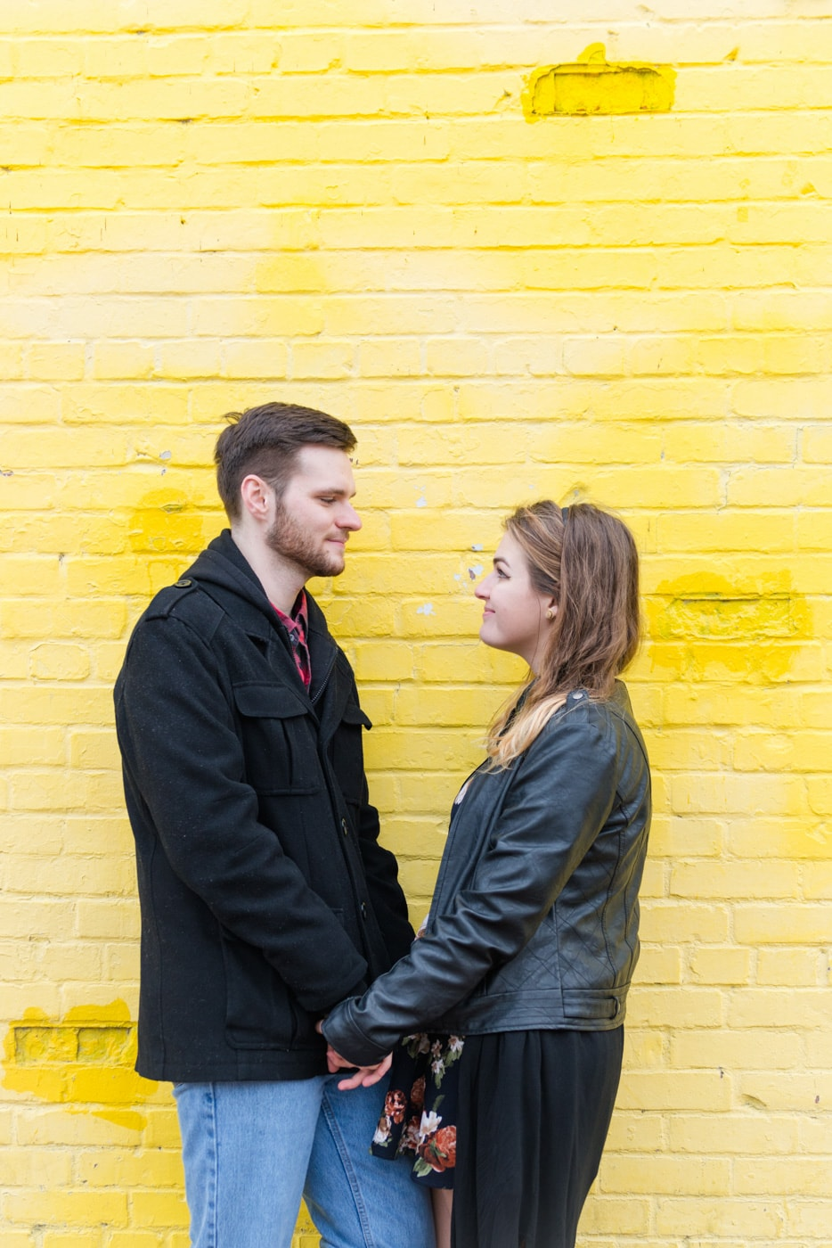 A young couple hold hands and look at each other by a yellow brick wall in Old Town Alexandria