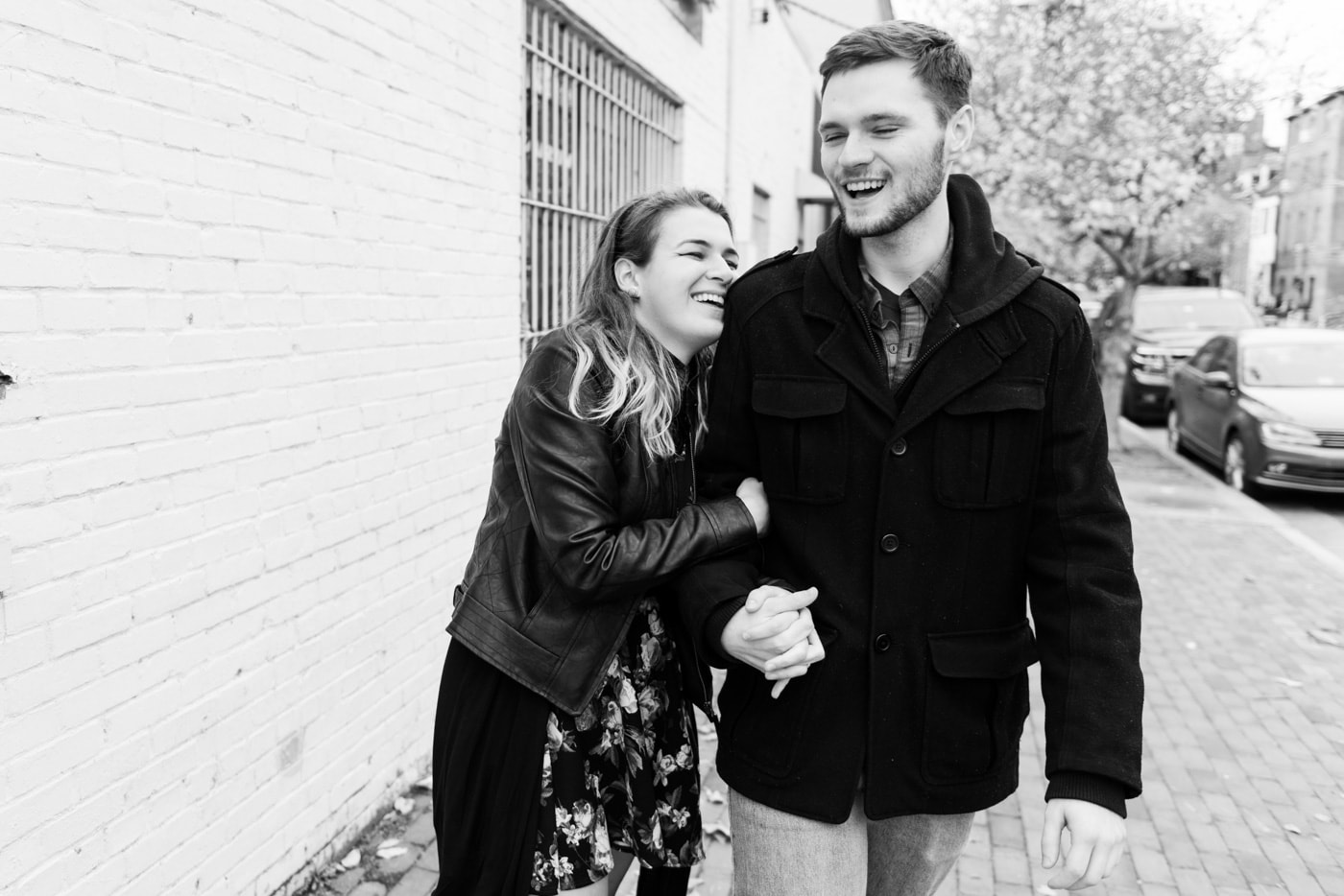 Black and white of a young couple holding hands and laughing as they walk down the sidewalk in old town alexandria