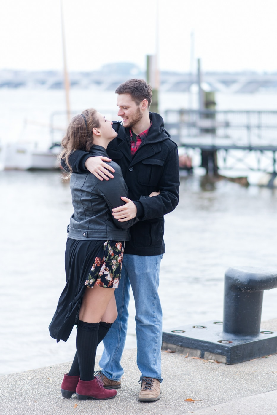 A young couple embrace and look at each other while standing by the water in Old Town Alexandria