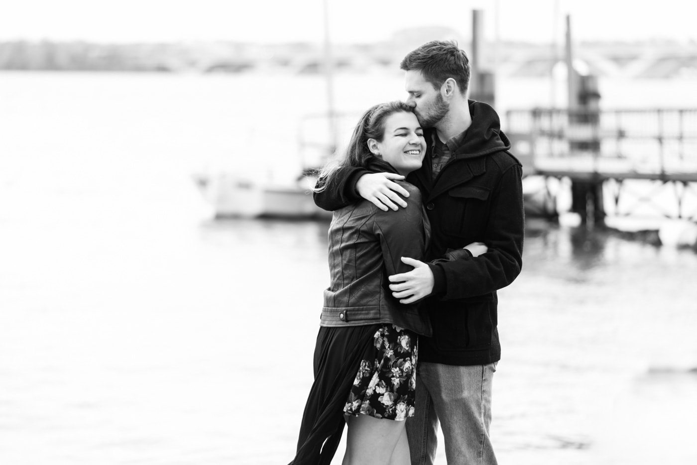 Black and white of a young couple embracing as he kisses the top of her head by the waterfront in Old Town Alexandria