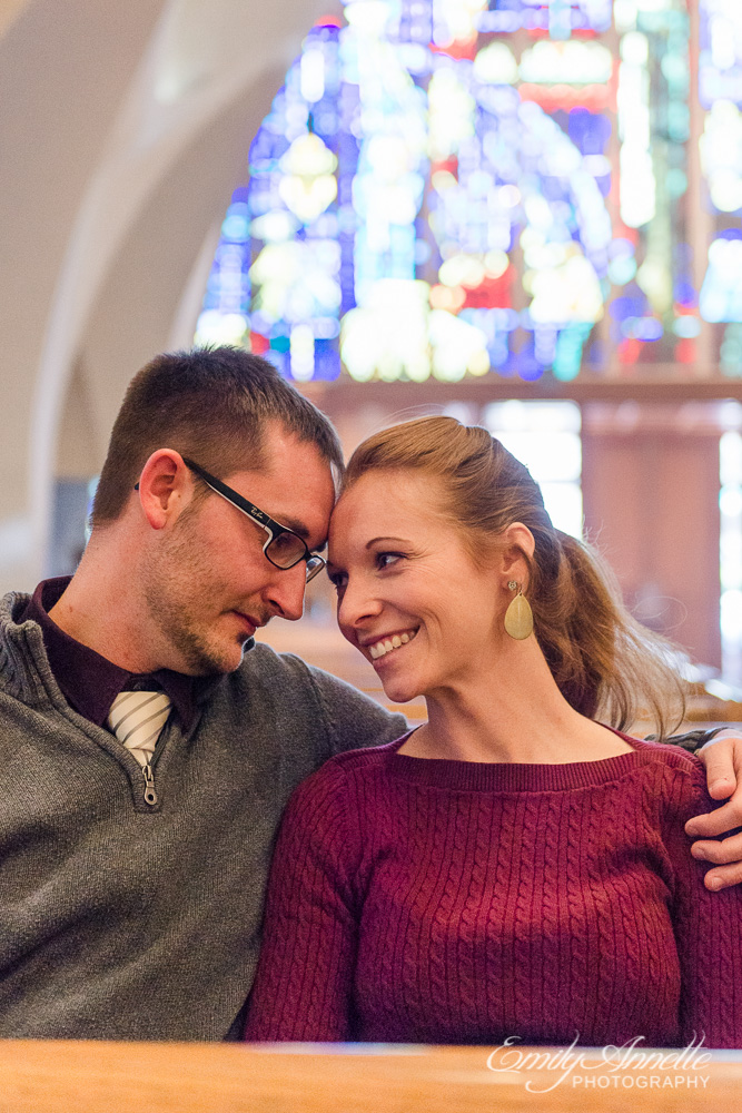 A young couple touch foreheads sitting in the pews at St Stephen Catholic Church in Washington DC