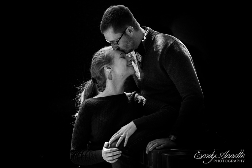 Black and white of a man sitting on a ledge kissing the forehead of his fiancee standing below him