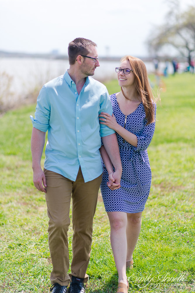 A young couple holding hands and looking at each other as they walk through gravelly point park in arlington, virginia