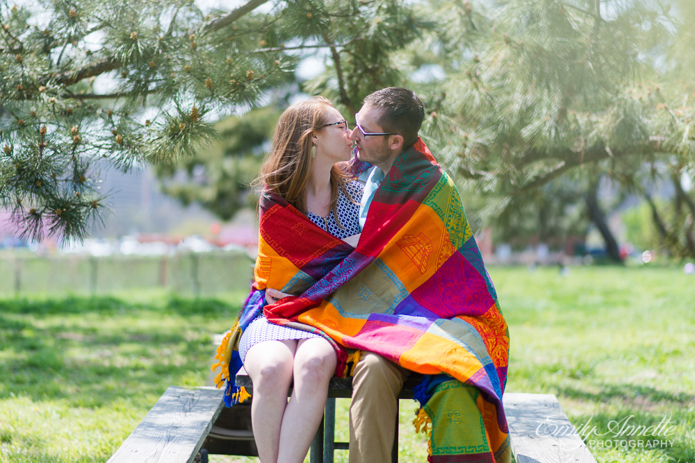 A young couple kiss while wrapped in a colorful blanket sitting on a picnic table at gravelly point park in washington, dc