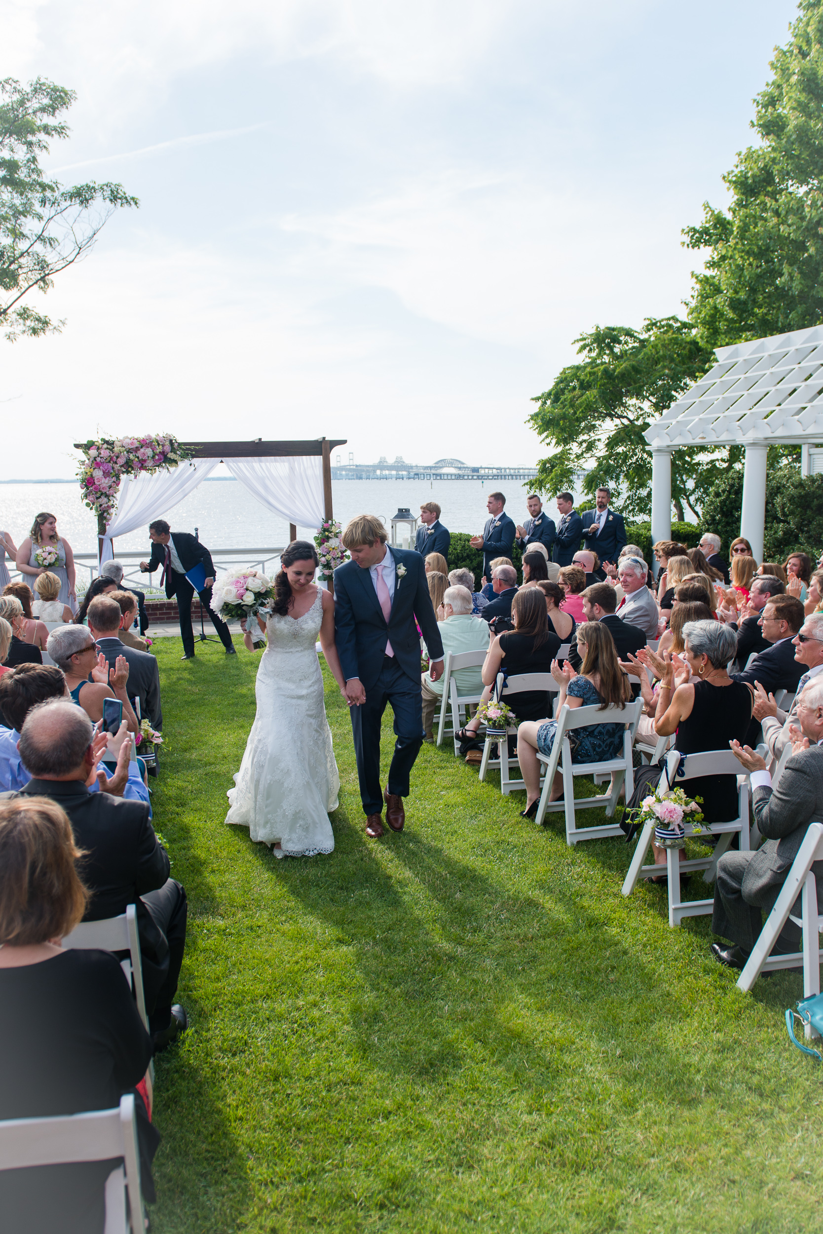the bride and groom process up the aisle as husband and wife after their wedding ceremony on the shore at the chesapeake bay beach club in stevensville, md