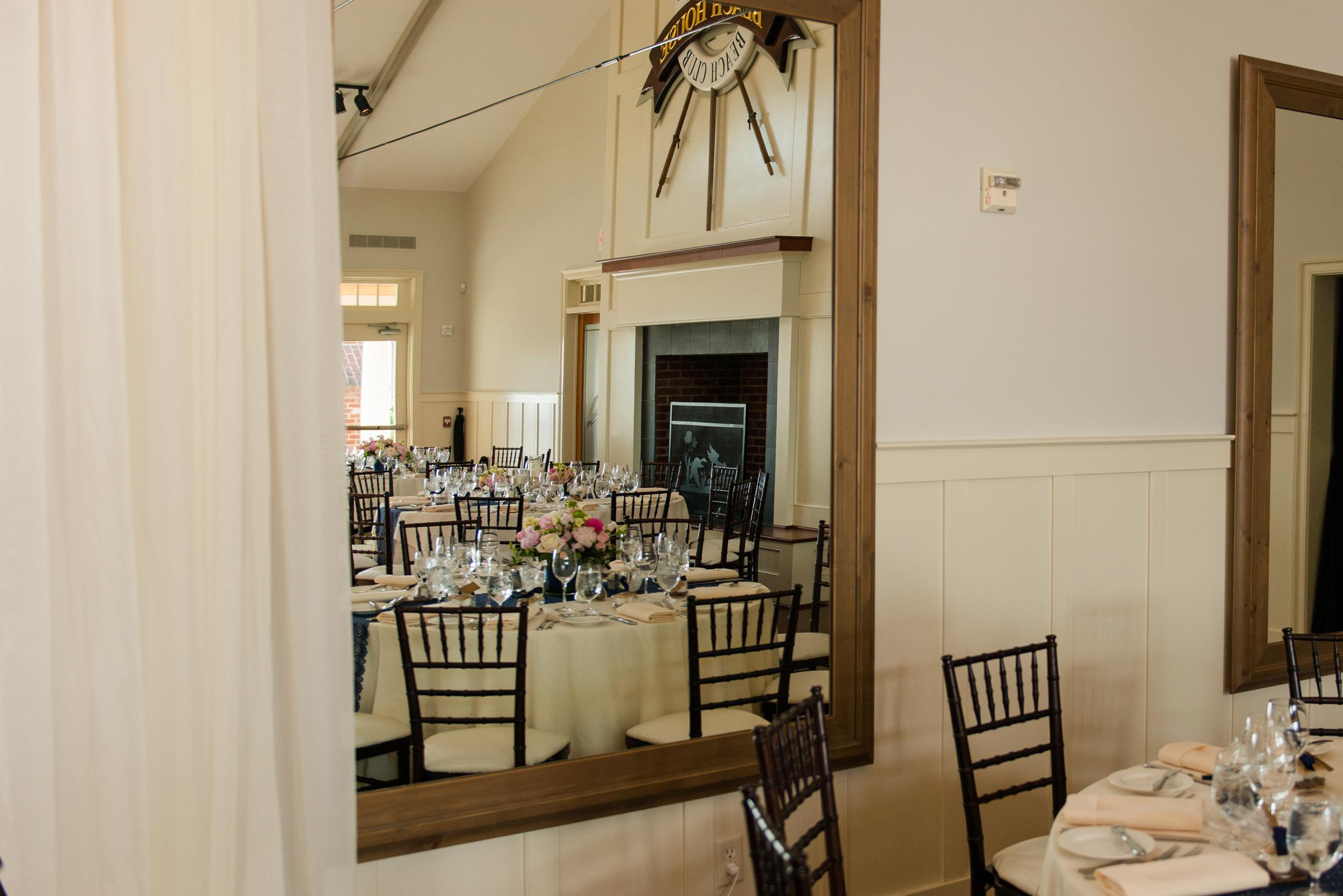 a view of a beachy wedding reception through a mirror in a ballroom at the chesapeake bay beach club in stevensville, md