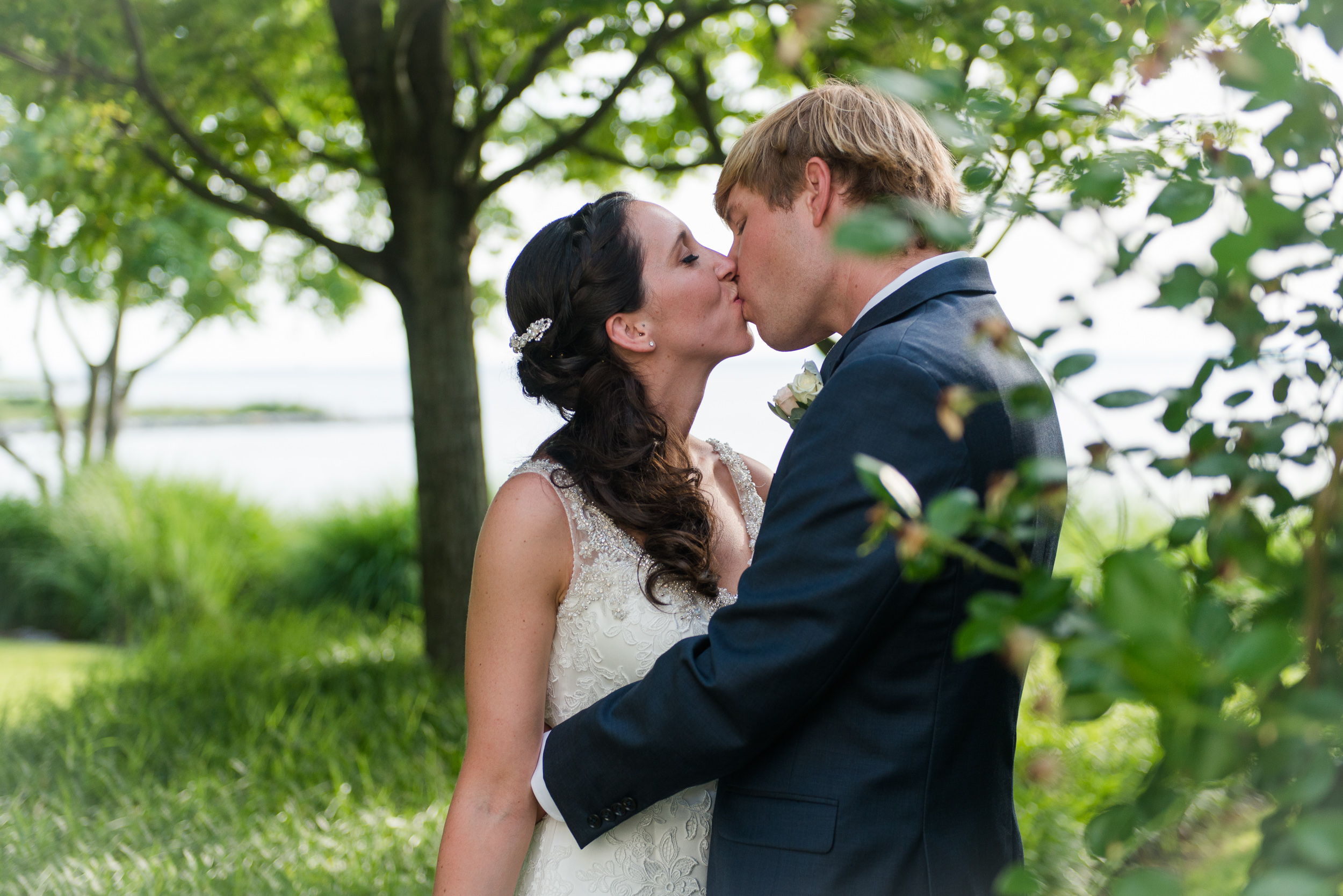 The bride and groom kiss in the woods by the chesapeake bay at the chesapeake bay beach club in stevensville, md