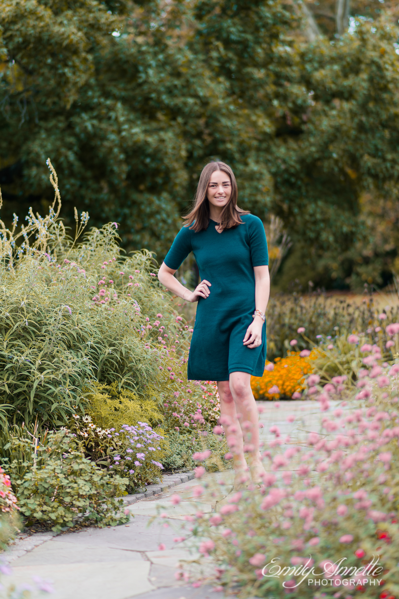 A young woman walks along a path through a lush garden in Green Spring Gardens in Fairfax, Virginia