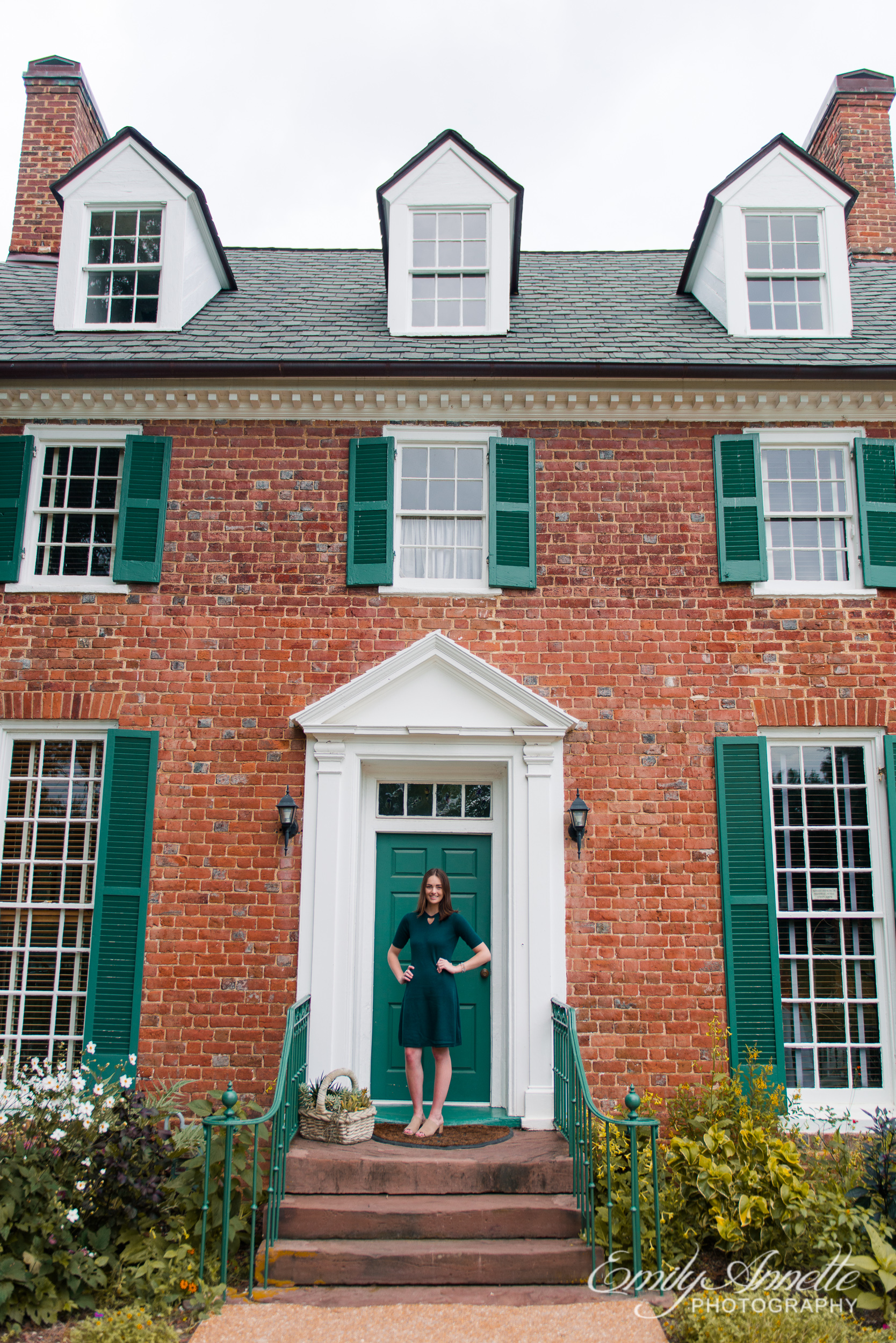 A young woman stands by the door of a historic house in Green Spring Gardens in Fairfax, Virginia