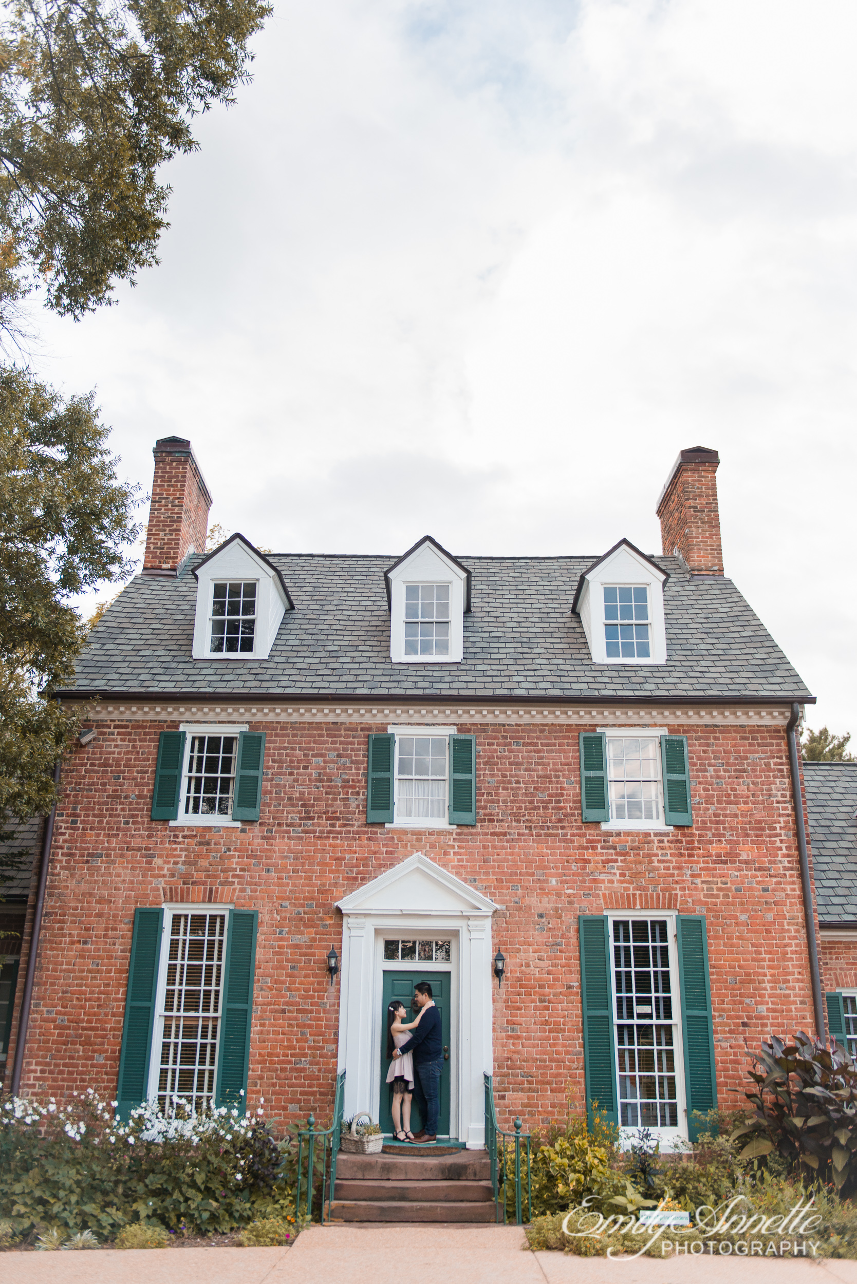 A couple stand in the doorway of a historic house at Green Spring Gardens Park in Fairfax, Virginia